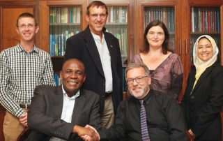 Seated, from left, Dr Khotso Mokhele from the Hans Merensky Foundation, and Professor Eugene Cloete from Stellenbosch University shake hands, with members from both institutions looking on. Image credit: Stellenbosch University