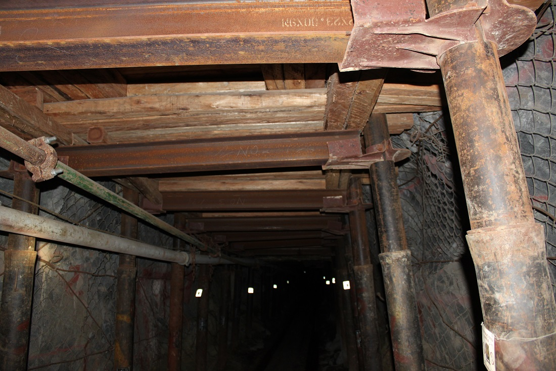 Timber planks are used to provide roof support in a corridor underground.