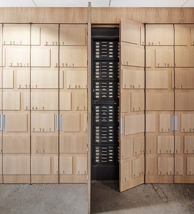 Thousands of slides, cassettes and discs are displayed and stored in a large wooden wall. Image credit: David Boyer