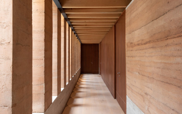The walls are composed of a lateral rhythm of rammed earth columns on one side, and wooden walls and doors on the other, dividing the volumes that house the bathrooms and dressing rooms. Photo by Alvaro Moragrega